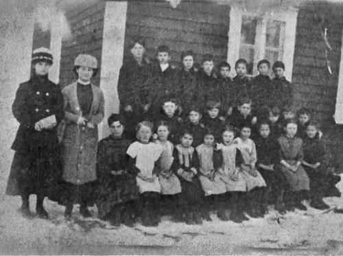 Des élèves bien sages pour la photo devant la première école, date : 1912, source : Notes historiques sur la paroisse de madeleine, 1980