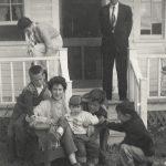 En famille : de g à d en avant : Hugues, Georgiana, Sylvianne, Pierre et André Lepage; sur la galerie : Rolande et l'oncle Jules, date : vers 1960, coll. : Langis Clavet